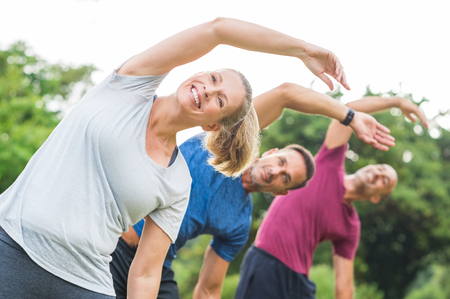sports training: Group of mature healthy people doing stretching at park. Fitness middle aged group exercising outdoor. Three happy people in a row doing stretching arm and smiling. Stock Photo
