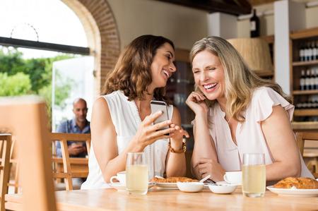 陽気な成熟した女性が携帯電話で面白いビデオを楽しみます。スマート フォン上の面白いメッセージを読んで成長した友人。朝食を食べながら笑い 写真素材
