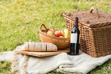 fruit: Picnic basket with bottle of wine, fruit and bread on tablecloth. Close up of food and drinks during picnic in a summer day. Red wine with picnic basket and healthy food on white blanket.