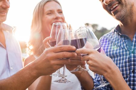 Groep volwassen vrienden verhogen van een toast met glazen rode wijn buitenshuis tijdens zonsondergang. Close-up handen van senior mannen en vrouwen roosteren met wijn. Close-up shot van de handen vrienden juichen.