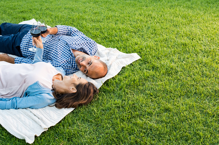 Mature happy couple lying down on grass raising a toast. Couple in park relaxing while drinking a glasses of red wine at picnic with copy space. Mature couple in love lying on blanket. Stock Photo