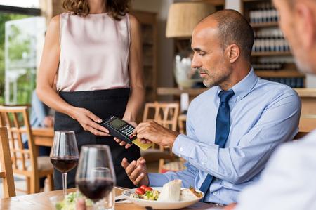 Camarero que sostiene la máquina golpe de tarjeta de crédito mientras que el código escribiendo cliente. hombre de negocios maduro que hace el pago en el café a través de tarjetas de crédito. Cliente que paga la factura del almuerzo con tarjeta de débito. Foto de archivo