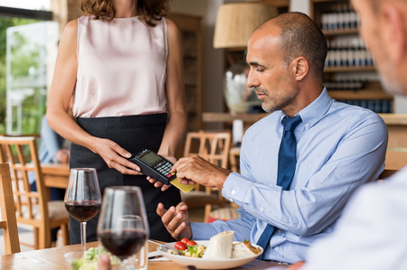 Waiter holding credit card swipe machine while customer typing code. Mature businessman making payment in cafe through credit card. Customer paying bill of lunch with debit card. Banque d'images