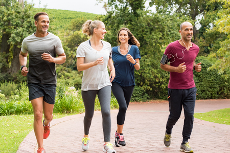Healthy group of people jogging on track in park. Happy couple enjoying friend time at jogging park while running. Mature friends running together outdoor. Stock Photo