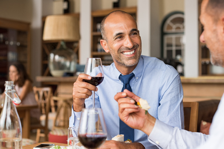 big: Two happy mature businessmen sitting in cafe and eating lunch. Two business colleagues meet in restaurant to discuss the deal. Smiling multiethnic businessman with his colleague after concluding a big deal. Stock Photo