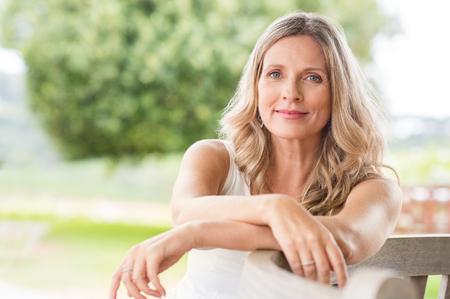 Gelukkige senior vrouw ontspannen op bank in het gazon. Close-up gezicht van een volwassen blonde vrouw lachend en kijken naar camera. Gepensioneerde vrouw in casuals zit buiten in een zomerdag. Stockfoto