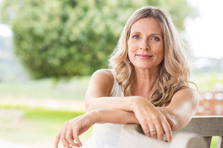 Happy senior woman relaxing on bench in the lawn. Close up face of a mature blonde woman smiling and looking at camera. Retired woman in casuals sitting outdoor in a summer day. Banco de Imagens - 75298836