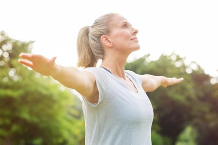 Mujer madura que hace yoga en el parque y que mira lejos. Mujer mayor rubia disfrutando de la naturaleza durante un ejercicio de respiración. Retrato de una mujer de la aptitud que estira los brazos y mirando lejos al aire libre.