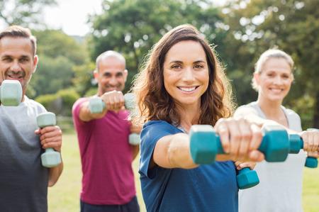 ejercicio aeróbico: Maduras personas en la sesión de entrenamiento de aeróbicos con pesas en el parque. Hombre feliz y mujer sonriente practicando fitness juntos al aire libre. Retrato de mujer madura haciendo ejercicio con otras personas en el fondo. Foto de archivo