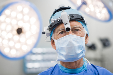 expertise: Senior cardiac surgeon with surgery equipment looking at camera. Portrait of a physician in a sterile operating room. Expertise surgeon with protective mask and cup in operating room. Stock Photo