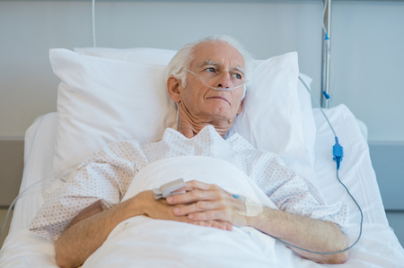Senior man with oxygen tube lying on hospital bed. Sad old patient feeling sick at hospital. Depressed old man hospitalized in a medical clinic.