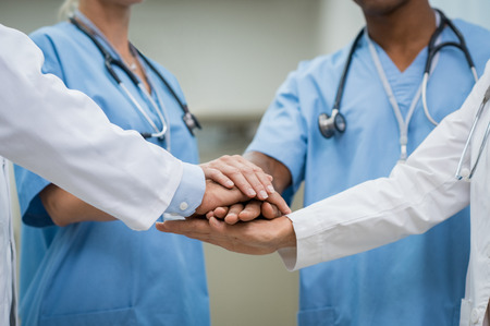 Mature doctors and young nurses stacking hands together at hospital. Close up hands of medical team stacking hands. Group of successful medical doctors and nurses stack of hands.