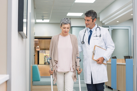 Mature doctor helping old female patient in crutches at the hospital. Physical therapist helping a woman on crutches in a medical clinic. Professional doctor and senior patient walking on hospital hallway.