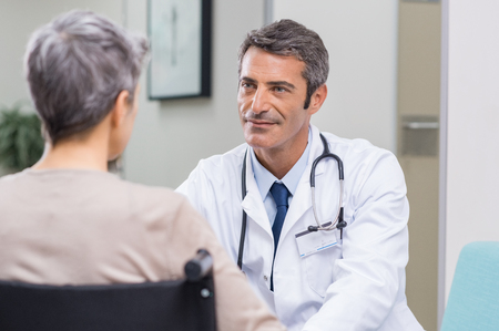 Doctor talking to woman in wheelchair after surgery. Portrait of a mature doctor talking to a senior disabled patient on wheelchair. Confident mature general practitioner in conversation at hospital. Stock Photo