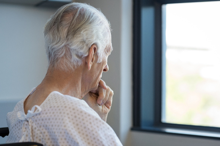 ailing: Rear view of a senior man sitting on wheelchair looking outside the window. Old man in hospital room sitting near window and thinking. Elderly patient feeling sad and alone at hospital.