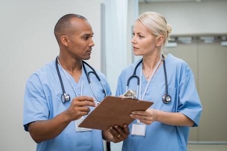 Giovani infermieri seri che discutono sul rapporto medico. Giovane dottore africano che controlla i dettagli del paziente prima di entrare nel teatro di funzionamento. Infermiera maschio e femminile che lavorano insieme alla clinica medica. Archivio Fotografico - 77149052