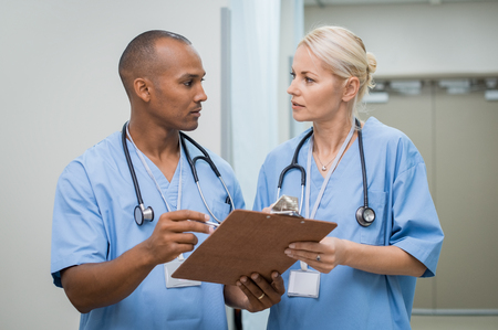 Young serious nurses discussing about medical report. Young african doctor checking patient details before entering operation theatre. Male and female nurse working together at medical clinic.