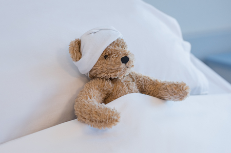 Injured teddy bear sleeping on hospital bed. Brown plush toy with a headache resting on bed. Sick brown bear with a bandage on his head lying in bed hospitalized at medical clinic. Stock Photo