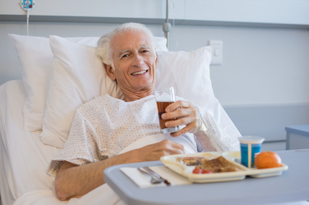 lunch meal: Senior patient eating his lunch on a tray in hospital and looking at camera. Portrait of old man eating a healthy meal in hospital room. Aged man enjoying meal in hospital while lying on bed. Stock Photo