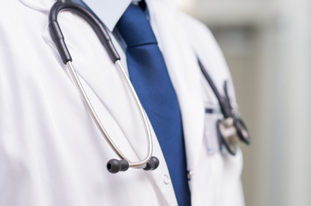 close up: Detail of a stethoscope on the neck of a doctor with tie. Close up of a doctor with white lab coat stethoscope at hospital. Medical male doctor with lab coat and stethoscope at clinic.