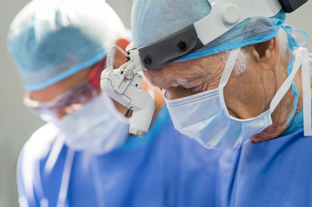 medical doctors: Senior surgeon operating with team of assistants. Skillful senior doctor is operating in surgery at hospital. Surgery team in the operating room.
