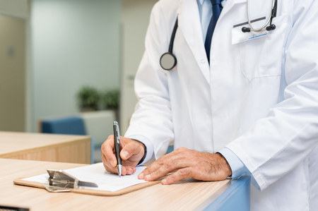 Close up hands of doctor writing on a document on clipboard. Senior surgeon checking form and making changes at reception desk. Male doctor reading patient information in a hospital.