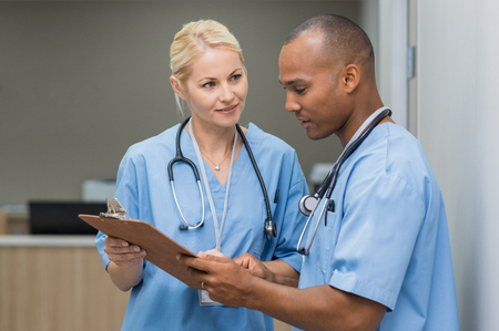 corridors: Medical multiethnic staff having discussion in a hospital hallway. Male and female nurse wearing blue scrubs working in a medical clinic. Two hospital workers discussing on laboratory test.