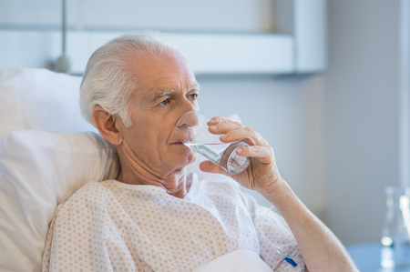 admitted: Senior patient in hospital drinking water. Old man recovering from disease in hospital drinking water after taking medicine. Aged man admitted to hospital resting on bed.