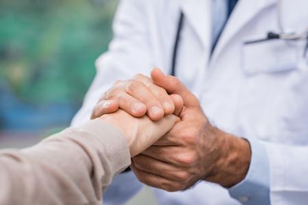 Close-up van dokter hand geruststelling haar vrouwelijke patiënt in het ziekenhuis. Close-up handen van de medische arts zorgvuldig met de handen van de patiënt. Vriendelijke arts die echte steun voor de patiënt geeft.