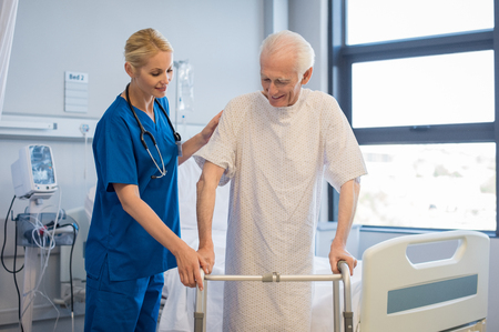 Nurse helping disabled man using walker in rehab center. Happy female nurse helping old patient to walk using walker in hospital. Doctor woman giving physical therapy to senior patient.