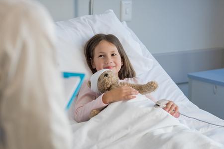 Petite fille souriante avec sonde saturée d'oxygène reposant sur le lit d'hôpital. Chose patient regardant le médecin avec un sourire. Enfant et médecin de la clinique médicale. Banque d'images - 77148688