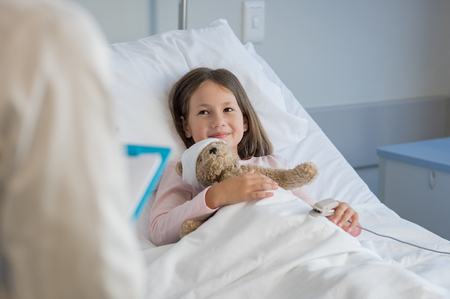 Smiling little girl with oxygen saturated probe resting on hospital bed. Girl patient looking at doctor with a smile. Child and doctor at medical clinic. Stock Photo