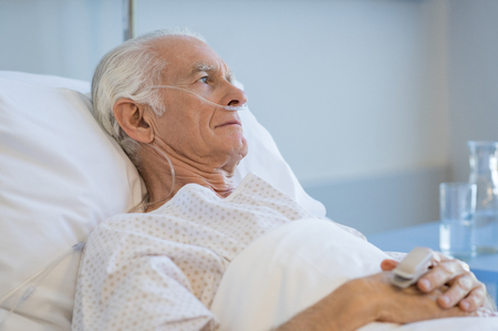 Sad senior man lying on hospital bed and looking away. Old patient with oxygen tube feeling lonely and thinking at hospital. Sick aged man lying hospitalized in a medical clinic. Foto de archivo