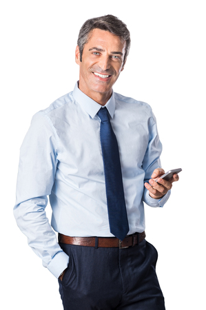 business: Relaxed mature business man typing message on smartphone and looking at camera. Portrait of a happy senior businessman using cell phone isolated on white background.  Stock Photo