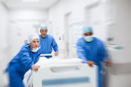 Nurse and doctor in a hurry taking patient to operation theatre. Patient on hospital bed pushed from surgeon to emergency theatre. Team of doctors and surgeon rushing patient. Stock Photo
