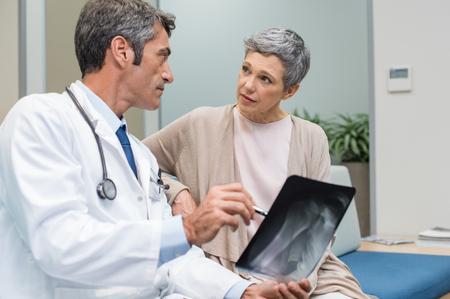 男性医師と議論するシニアの患者は、オフィスでの結果をスキャンします。医師は診療所の年配の女性の x 線を表示します。成熟した医師は、彼の