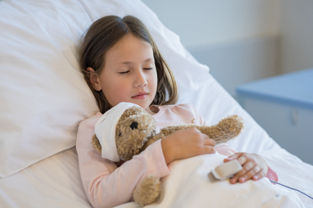Cute girl sleeping in hospital bed with teddy bear. Little girl resting in hospital while hugging her teddy bear. Ill child at medical clinic. Stock Photo