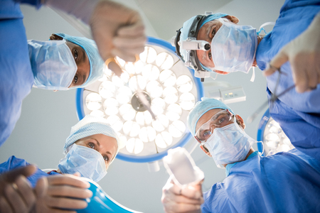 Surgeons team at work in operating room. Below view of surgeons holding medical instruments in hands and looking at patient. Multiethnic doctors wearing protective uniforms while operating.