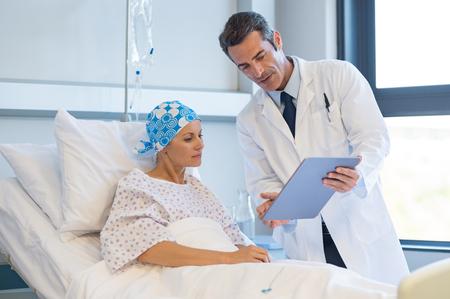 Doctor diciendo a la mujer paciente los resultados de sus pruebas médicas. Médico mostrando los registros médicos a un paciente de cáncer en la sala de hospital. Un médico mayor explica los efectos secundarios de la intervención. Foto de archivo - 77148892