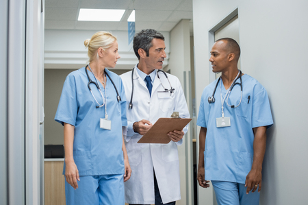 medical doctors: Mature doctor discussing with african male nurse in a hallway hospital. Doctor discussing patient case status with his medical staff after operation. Doctor holding clipboard while in conversation with nurse.