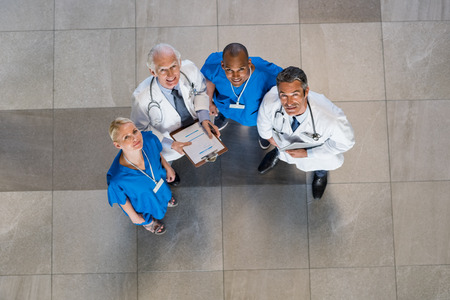 medical doctors: High angle view of doctors and nurses looking at camera during a conference. Cheerful nurses and multiethnic doctors smiling in a modern hospital hallway. Team of medical people in clinic.