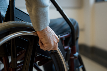 Paralyzed old man using his wheelchair. Closeup of hand of disabled man pushing wheel of wheelchair. Detail of hand of senior man holding the wheel of wheelchair.