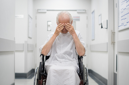 Stressed senior patient sitting on wheelchair in hospital corridor. Lonely old man cover his eyes with hands in hospital hallway. Elderly disabled patient feeling sad and abandoned.