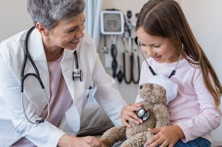 Happy little girl checking heartbeat of teddy bear in hospital. Happy pediatrician and child patient playing with stuff toy. Little girl and senior doctor with stethoscope auscultate the heartbeat of the ill teddy bear. Stock Photo
