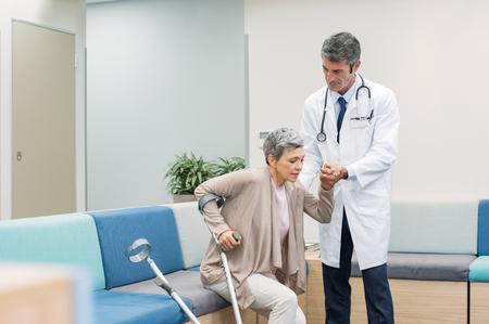 Arts helpt patiënt met krukken om op te staan in een ziekenhuis. Senior vrouwelijke patiënt die hulp van volwassen arts krijgt om op te staan. Vrouw met gebroken been met ondersteuning van dokter en krukken om op te staan op medische kliniek.
