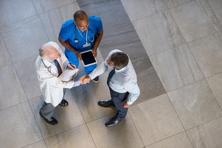 製薬会社の代表に手を振って先輩医師の高角度のビュー。病院で医師と握手ビジネスマンの平面図です。ビジネスマンは、医師と契約を締結します