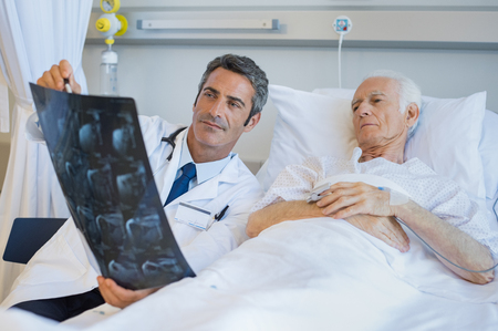 admitted: Senior doctor explaining xray to patient lying on hospital bed. Surgeon showing radiology report to old man admitted to hospital. Male doctor take care of his patient. Stock Photo