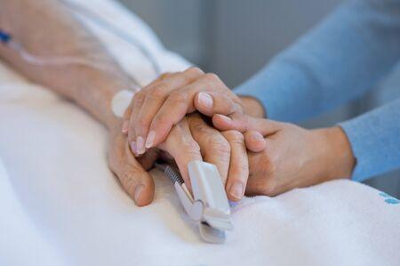 Fille tenant la main d'un père âgé. Gros plan d'une femme tenant un homme âgé dans l'hôpital. Gros plan d'une infirmière qui tient la main du vieux homme avec une sonde saturée d'oxygène sur le doigt. Banque d'images - 77149054