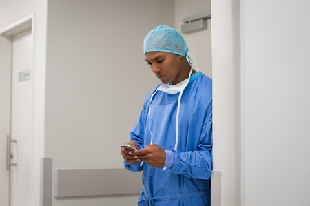 screen: Portrait of surgeon reading message at mobile phone. Young surgeon using cell phone in hospital to commiunicate with transport organs. African doctor using smartphone outside the operating room. Stock Photo