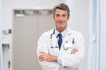 의료 클리닉에서 그의 목 주위 청진 기와 웃는 의사의 초상화. 병원 로비에서 행복 한 미소 의사입니다. 성숙한 남자 주요 작업 후 자신감과 카메라를
